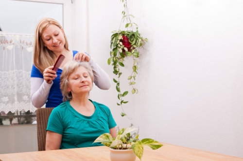 caregiver combing an elderly woman's hair