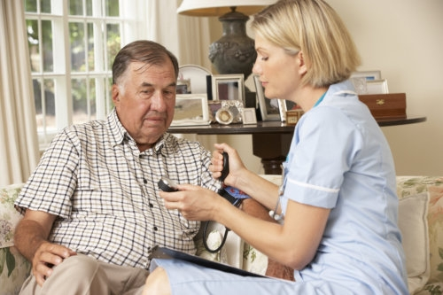 retired senior man gaving health check with nurse at home