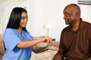 caregiver giving medicine to an elderly man